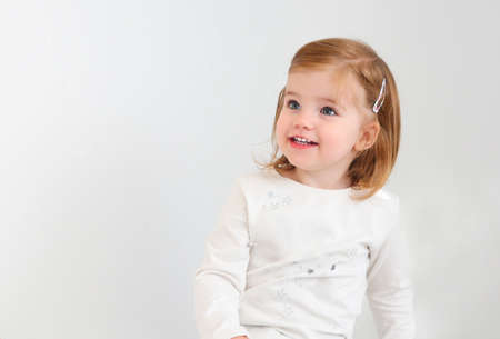 Cute smiling toddler girl looking away isolated on white 版權商用圖片