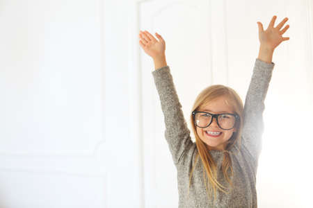 Smiling cute little girl with black eyeglasses over white background.  Education, school, childhood, people and vision concept 版權商用圖片