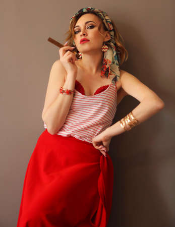 Portrait of beautiful woman in bright clothing and bow in head with bright lips holding cigar and smoking looking forward in studio on brown background