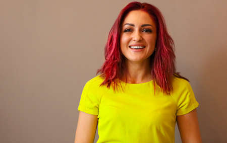 Emotional portrait of a woman with pink hair wearing yellow dress on a wall background 版權商用圖片