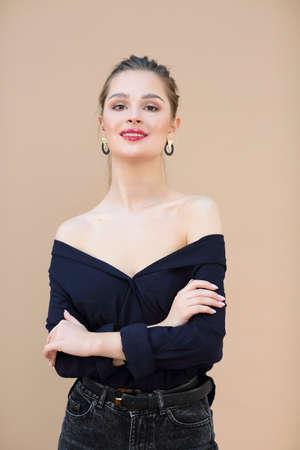 Smiling fashion model wearing navy blue blouse on beige background