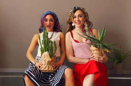 Portrait of two beautiful women in bright clothing and bow in head with bright lips holding cactuses in studio on brown background 版權商用圖片