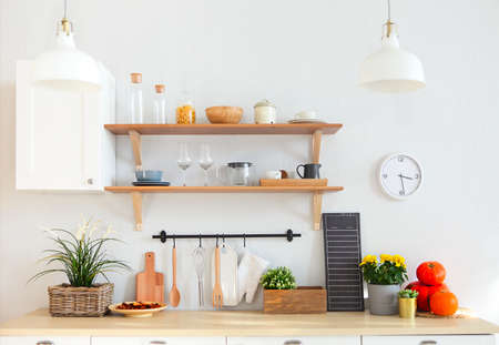Interior of empty modern white kitchen with various objects on the table