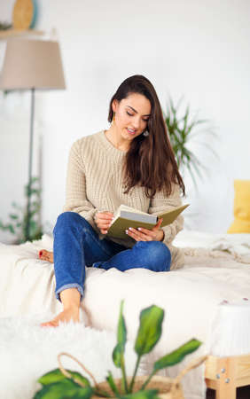 Young happy brunette woman with book wearing sweater at home Stock Photo