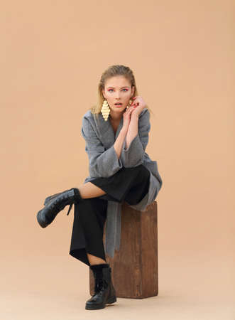 High fashion portrait of young elegant woman in Grey coat, black pants, black ankle boots and gold earrings on beige background