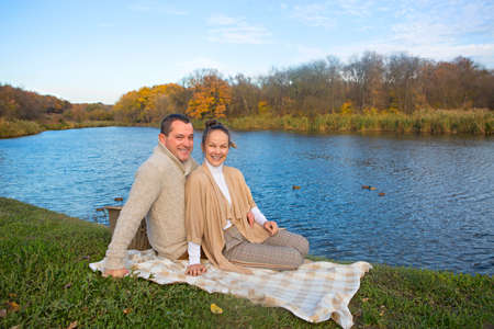 Young couple in love chilling by autumn lake. Happy man and woman enjoying nature and hugging. Romantic date