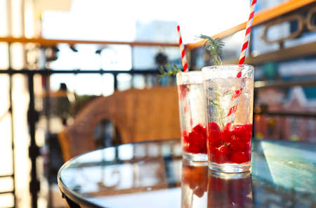 Summer refreshing lemonade with rasberry on a balcony of terrace, paper straw on the glasses. Sunset