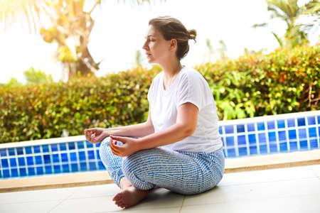 Frau, die mit bekleideten Augen am Pool meditiert. Tropical bsckground Standard-Bild