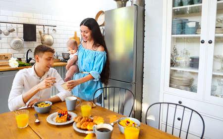 Happy family little baby boy having breakfast In the kitchen