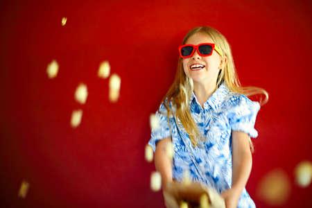Little girl wearing sunglasses and eating popcorn having fun 版權商用圖片