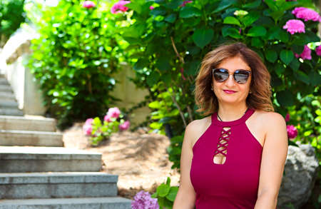 Portrait of a lovely middle aged woman wearing sunglasses having fun outdoors while relaxing in the garden
