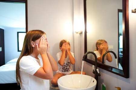 Happy children girls are washing their faces in a bathroom together