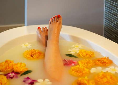 Young woman resting in bath with milk and flowers Zdjęcie Seryjne