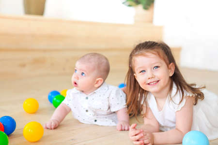 Baby boy and his sister playing with balls. Colorful toys for kids. Kids in play room. Toddler kid and little child with balls for children. 写真素材