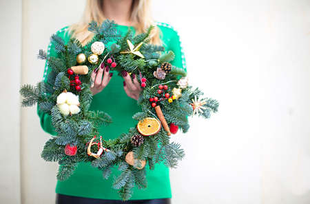 Woman holding Christmas wreath maked by herself. Close up Stok Fotoğraf