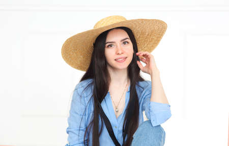 Beautiful smiling woman in straw hat and blue shirt looking at camera and posing on light background