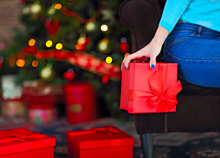 Smiling happy woman with gift box over living room on Christmas tree background. Holidays and people concept. Xmas time