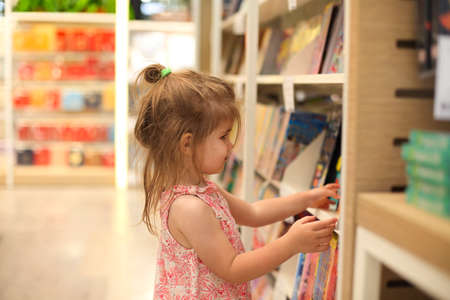 Little cute child picking books from the bookshelf in book store 版權商用圖片