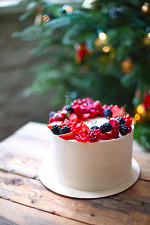 Christmas Cake decorated with berries by the Christmas tree 版權商用圖片