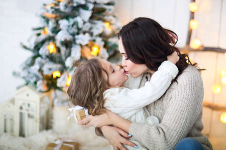 Beautiful happy mother with lher ittle daughter in knit sweater sitting on the background of Christmas interior hugging together and smiling 版權商用圖片