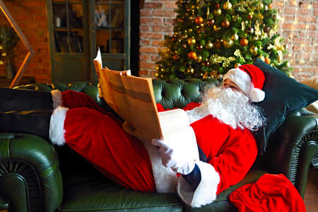 Santa claus reading business newspaper while sitting on green sofa
