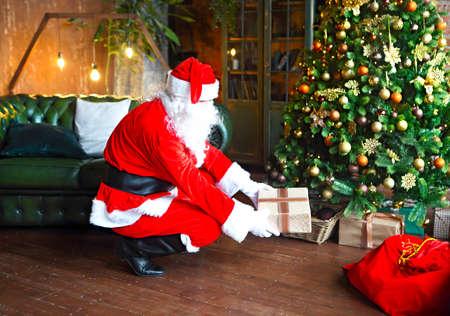Santa Claus secretly putting gift boxes under the Christmas tree. Xmas 版權商用圖片