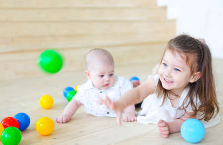 Baby boy and his sister playing with balls. Colorful toys for kids. Kids in play room. Toddler kid and little child with balls for children. 版權商用圖片