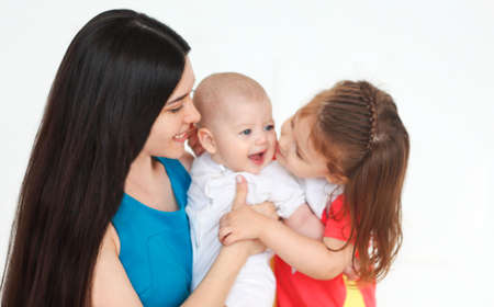 Happy young mother and cute little kids spending time together and smiling at camera
