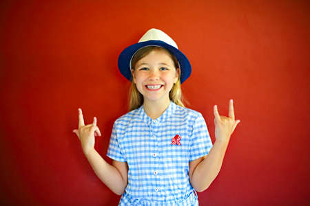 Pretty emothional children wear a hat on a red background. Copy space, daylight