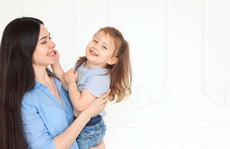 Happy young bright mother hugging her little daughter having fun together