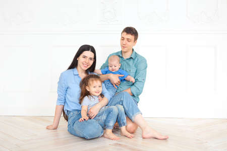 Happy young parents with their adorable little kids at home having fun together Stockfoto