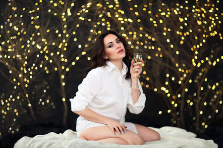 Smiling woman in white shit with glass of champagne over lights background. Party, drinks, holidays, luxury, friendship and celebration concept 版權商用圖片