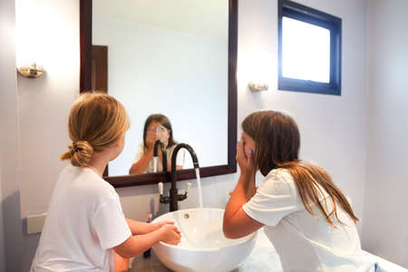 Happy children girls are washing their faces in a bathroom together 版權商用圖片