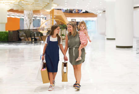 Mother and daughters walking with shopping bags on storefronts background