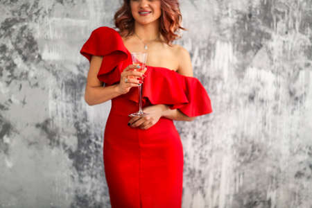 Smiling woman in red dress with a glass of champagne. Close up. Party concept