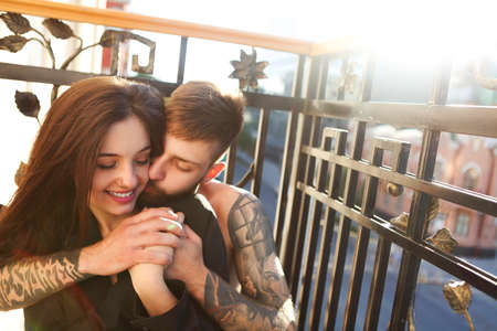 Young tattooed stylish couple in love hugging on the balcony
