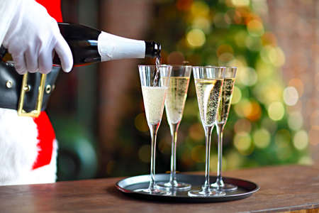 Santa Claus holding champagne glasses on the tray. Closeup