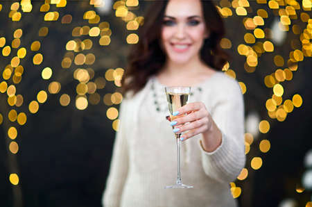 Smiling woman in the sweater with glass of champagne over lights background. Party, drinks, holidays, luxury, friendship and celebration concept 写真素材