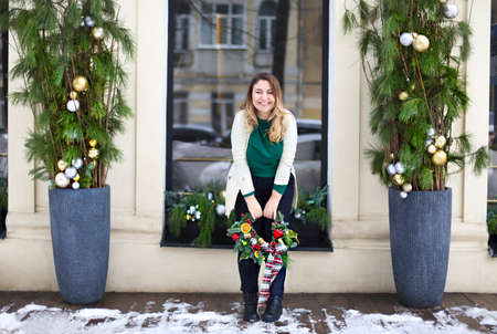 Happy woman holding Christmas wreath maked by herself