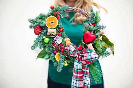 Woman holding Christmas wreath maked by herself. Close up 版權商用圖片