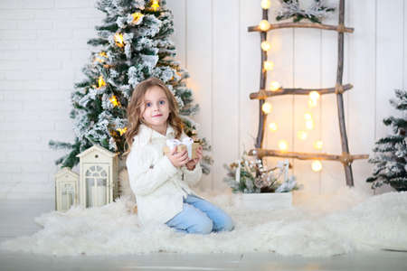 Happy little girl unpacking christmas gift at Christmas decoration
