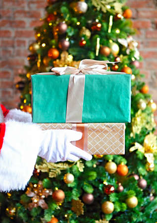 Santa Claus secretly putting gift boxes by the Christmas tree. Xmas