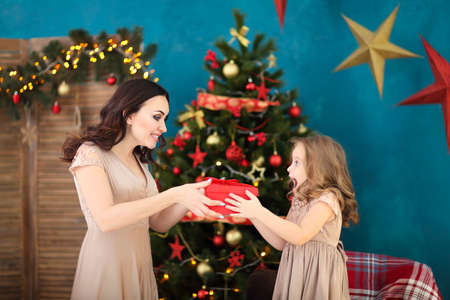 Beautiful happy mother with her ittle daughter on the background of Christmas interior holding present together and smiling  版權商用圖片