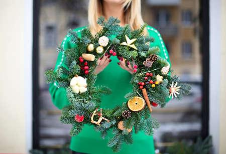 Girl holding Christmas wreath maked by herself outdoors. Christmas concept. Xmas mood 版權商用圖片