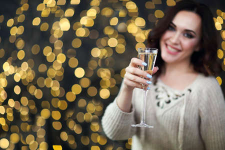 Smiling woman in the sweater with glass of champagne over lights background. Party, drinks, holidays, luxury, friendship and celebration concept 版權商用圖片