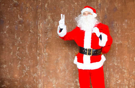 Santa Claus walking with the big red bag of the presents on the brown background