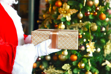 Santa Claus secretly putting gift box by the Christmas tree. Xmas