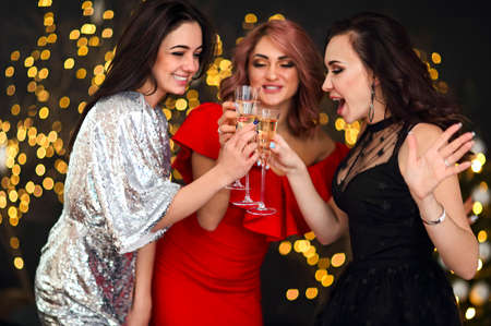 Smiling women in evening dresses with glasses of champagne over lights background. Party, drinks, holidays, luxury, friendship and celebration concept 版權商用圖片