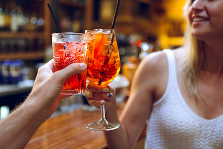 Woman and man raising a glasses of coktails in the bar background 免版税图像 - 133884964