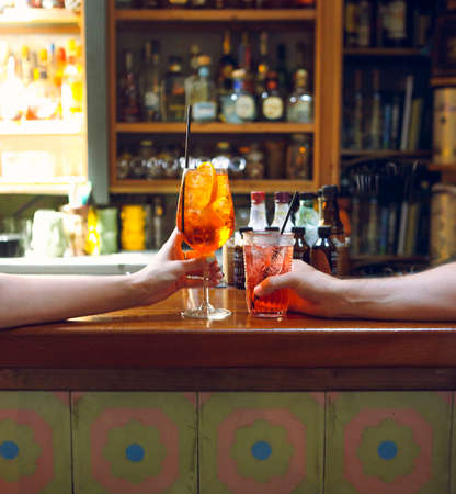 Woman and man raising a glasses of coktails in the bar background